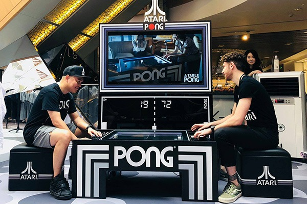 Two guys playing Pong® on the Atari Pong® Coffee table