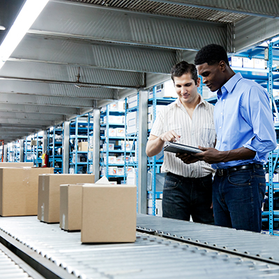 Two men in front of conveyor belt of boxes