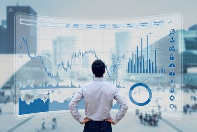 man standing in front of financial screen