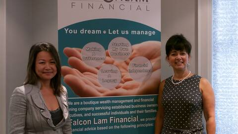 Image of falcon lam employees standing by a banner