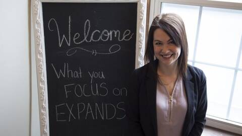 image of nicole standing next to a chalkboard that says welcome