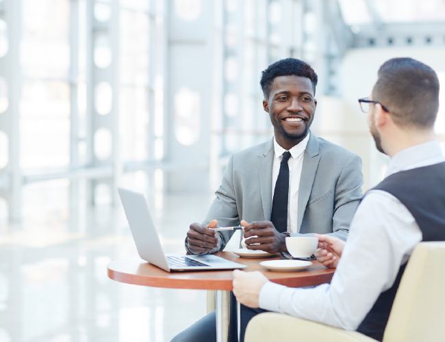 Image of two men sitting and discussing a business plan