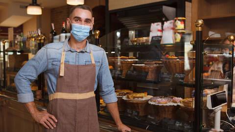 Male baker wearing medical face mask working at his bakery store during coronavirus quarantine